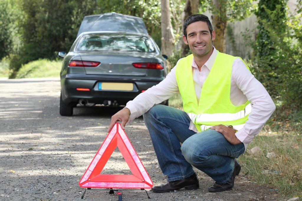 man putting an alert sign in front of a car
