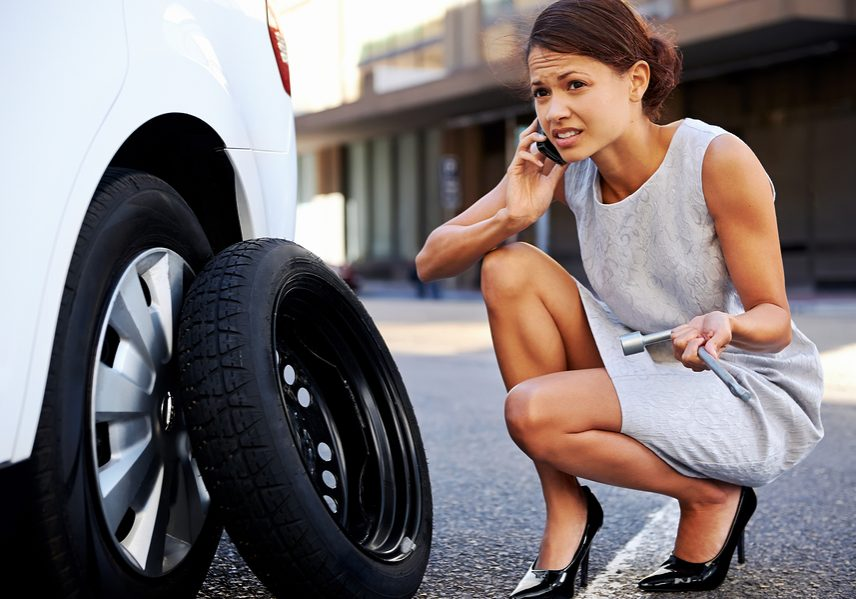 woman is having a hard time changing her tire